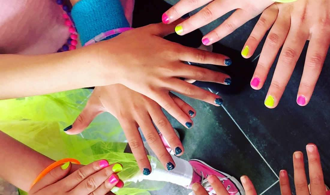 Several hands with brightly coloured party nails