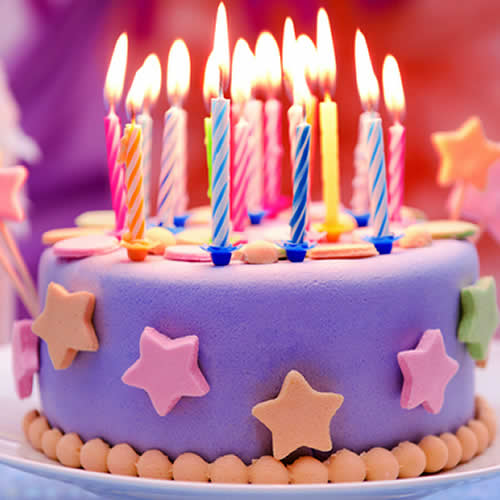 Candles lit on a purple birthday cake